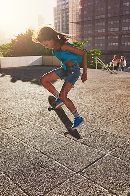 Buy stock photo Shot of a young woman skating in the city