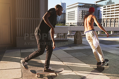 Buy stock photo Shot of two young men skating in the city
