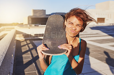 Buy stock photo Shot of a young woman holding her skateboard while making a face
