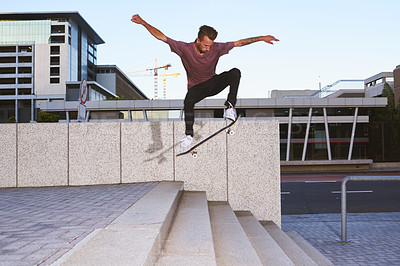 Buy stock photo Shot of a young man skating down a flight of stairs