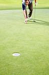 Male golfer placing the ball to putt