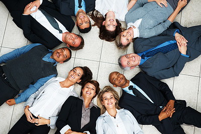 Buy stock photo Top view of colleagues lying down on floor, looking up