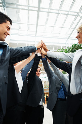Buy stock photo Low angle view of colleagues holding up their hands as one
