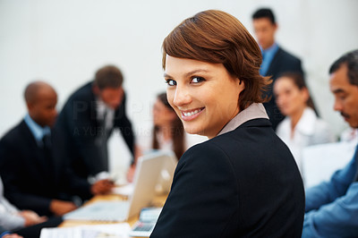 Buy stock photo Young female executive looking at you with colleagues in background