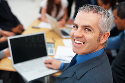 Buy stock photo Closeup of smiling male executive with team in background
