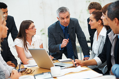 Buy stock photo Colleagues listening to their leader during meeting