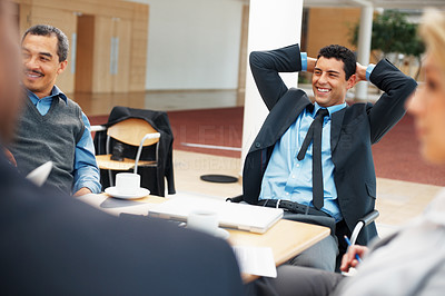 Buy stock photo Focus on happy executive relaxing in chair during business meeting