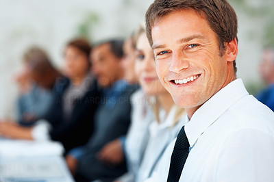 Buy stock photo Closeup of handsome businessman with colleagues in distance