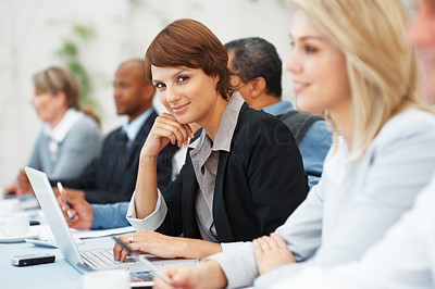 Buy stock photo Cute female executive with laptop smiling at the camera during a corporate meeting