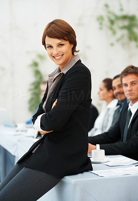 Buy stock photo Portrait of happy woman sitting on a table with colleagues in background