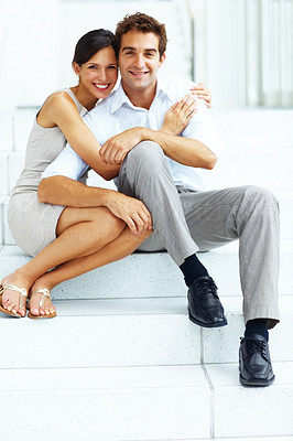 Buy stock photo Portrait of cute young love couple sitting together on steps of a building