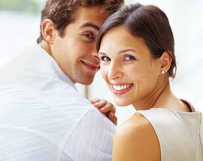 Buy stock photo Closeup of beautiful young couple looking behind at you while sitting together