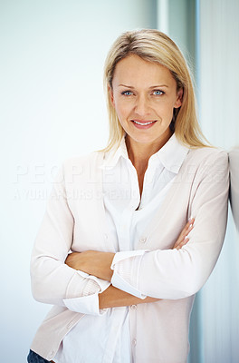 Buy stock photo Portrait of a smiling casual businesswoman posing with her hand folded against grey background