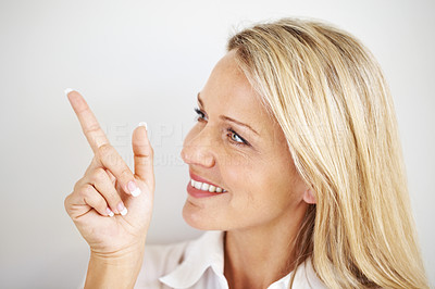 Buy stock photo Closeup portrait of pretty happy young woman pointing at copyspace