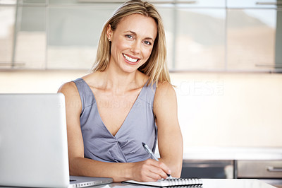 Buy stock photo Portrait of a beautiful blond female using laptop making note in notepad - Indoor