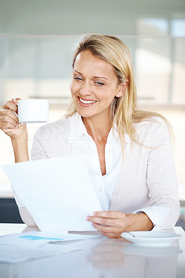 Buy stock photo Portrait of a smart young businesswoman reading paper and drinking coffee at office