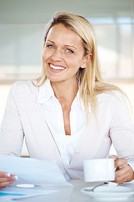 Buy stock photo Pretty young businesswoman holding a cup and working on document at office