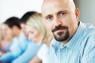 Buy stock photo Closeup of a mature businessman sitting in a meeting with his colleagues in background at office
