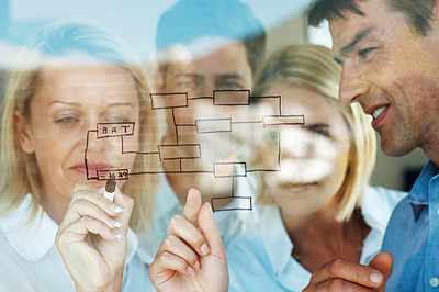 Buy stock photo Confident businesswoman drawing a chart of growth on glass with her business colleagues at the office