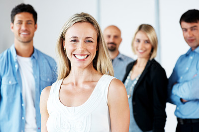 Buy stock photo Portrait of a cheerful young woman standing with her business colleagues at back