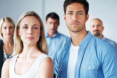Buy stock photo Portrait of a confident young man and woman standing with people in background
