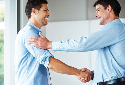 Buy stock photo Portrait of a smiling young businessman shaking hand with colleague at office