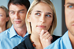 Thoughtful young businesswoman standing in row with colleagues