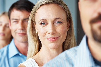 Buy stock photo Portrait of a cute young businesswoman smiling while standing in row with colleagues