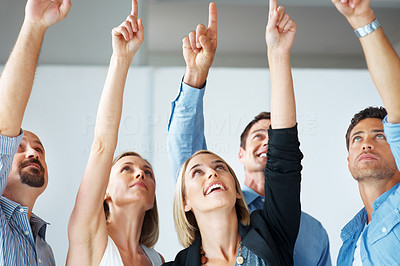 Buy stock photo Group of happy young business people standing together pointing and looking up
