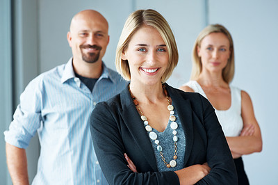 Buy stock photo Portrait of a charming business woman standing with her hands folded and the team in background