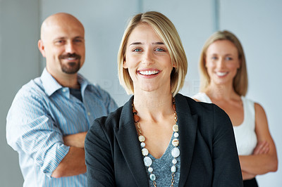 Buy stock photo Portrait of a stylish young business woman with her colleagues in background