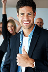Business success - Excited businessman with thumbs up and team at back