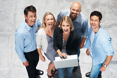 Buy stock photo Top view of happy group of business people working on a laptop and looking up