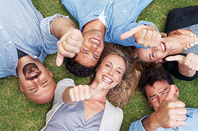 Buy stock photo Portrait of a group of people lying together on grass with thumbs up