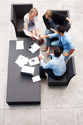 Buy stock photo Top view of a group of business people sitting together and working on business project - Teamwork