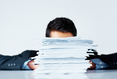 Buy stock photo Focus on stack of papers with executive in background