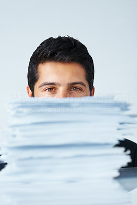 Buy stock photo Focus on businessman sitting behind stack of papers