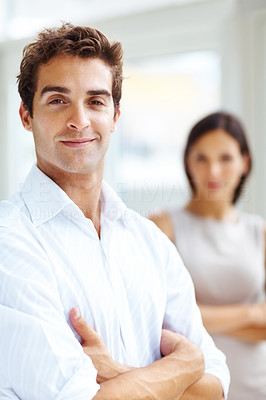 Buy stock photo Portrait of happy young man standing with his hands folded and a woman at the back