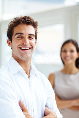 Buy stock photo Portrait of handsome young man standing with his hands folded and a woman at the back