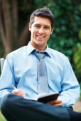 Buy stock photo Happy young business man writing outdoors