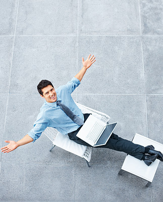 Buy stock photo Top view of executive sitting in a chair smiling with his arms out and a laptop on his lap - copyspace