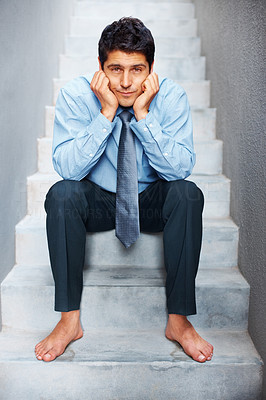 Buy stock photo Business man resting his chin in hands looking dejected while sitting barefoot on concrtete stairs - conceptual