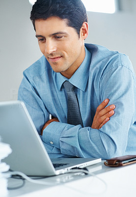 Buy stock photo Businessman sitting with arms folded at desk in front of laptop