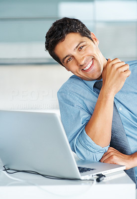 Buy stock photo Businessman casually sitting next to laptop with head tilted