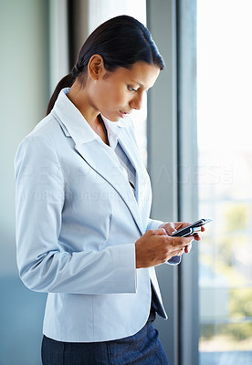 Buy stock photo Business woman dialing cell phone while standing near window