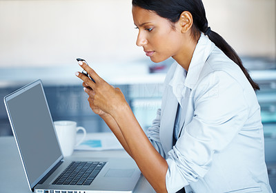 Buy stock photo Female executive holding cell phone and working on laptop
