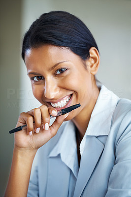 Buy stock photo Portrait of pretty woman smiling while holding pen up to face