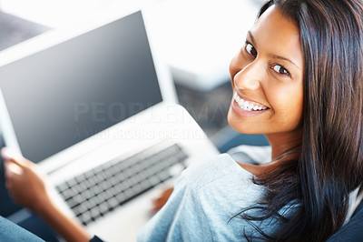 Buy stock photo Gorgeous young woman working on laptop indoors with a smile - portrait
