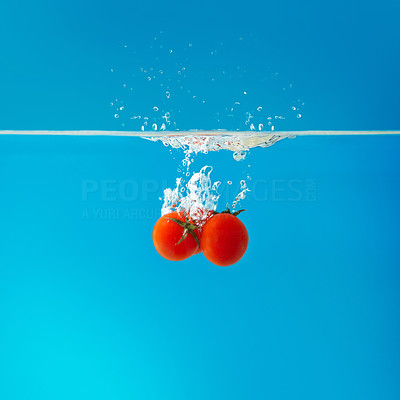 Buy stock photo View of small tomatoes falling into water against blue background
