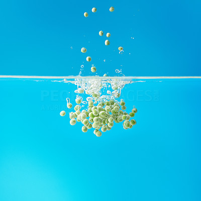 Buy stock photo Group of peas splashing in water against blue background
